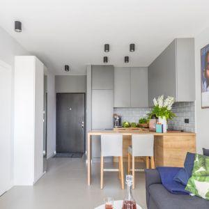 Mały salon w bloku - aneks kuchenny i część dzienna urządzone w jasnych kolorach. Projekt: Decoroom. Fot. Pion Poziom