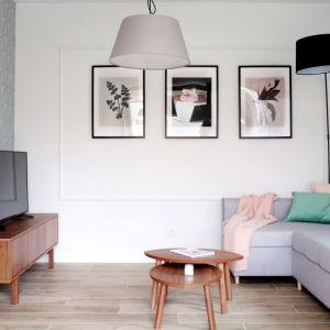 Mały salon w bloku, urządzony w jasnych kolorach, z ciekawą tapetą na ścianie z telewizorem. Dekorian Home x Grid Studio Projektowe, fot. Norbert Adamowicz