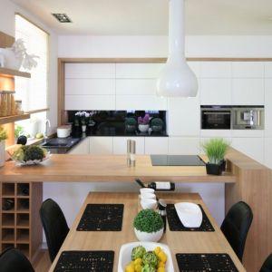 Białe meble zamknięte w drewniane ramy nadają kuchni ciepłego, przytulnego klimatu.  Projekt Małgorzata Błaszczak. Fot. Bartosz Jarosz