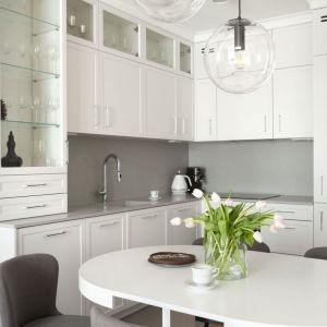 Ściana nad blatem w kuchni wykończona jest pasem praktycznych, szarych płytek. Projekt: Studio Projektowania Miśkiewicz Design. Fot. Anna Powałowska