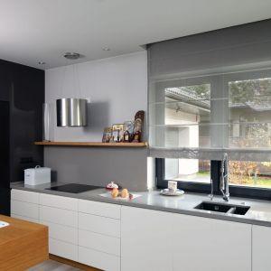 Ściana nad blatem w kuchni zdobi szkło w szarym kolorze. Projekt: Laura Sulzik. Fot. Bartosz Jarosz