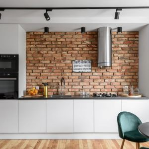 Ścianę nad blatem w kuchni wykończona jest cegłą. Cegła ułożona na całej ścianie prezentuje się bardzo efektownie. Projekt: Magdalena i Robert Scheitza, pracownia SHLTR Architekci