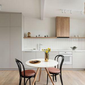Ściana nad blatem w kuchni wykończona jest białymi płytkami. Idealnie pasują one do jasnych mebli oraz do drewnianych elementów. Projekt: Ola Dąbrówka, GOOD VIBES Interiors. Fot. Mikołaj Dąbrowski