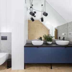 W łazience znajdziemy połączenie płytek układanych w jodełkę i szarego lastryko. Projekt: Joanna Ochota (Concept JOana). Fot. Jaga Kraupe