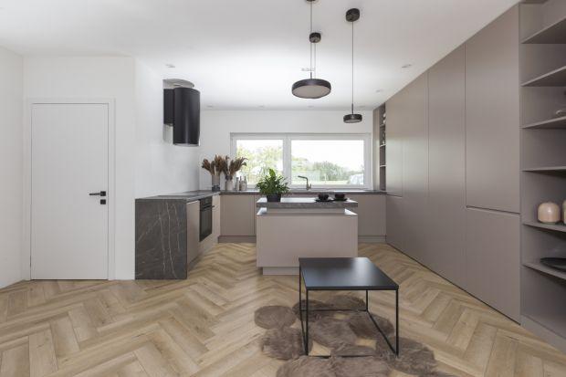 Wnętrze jest nowoczesne, proste i funkcjonalne. Spokojna, stonowana kolorystykapięknie łączy się z eleganckim wzorem jodełki ułożonym na podłodze. Właściciele mają tu wszystko, czego potrzebują do życia.