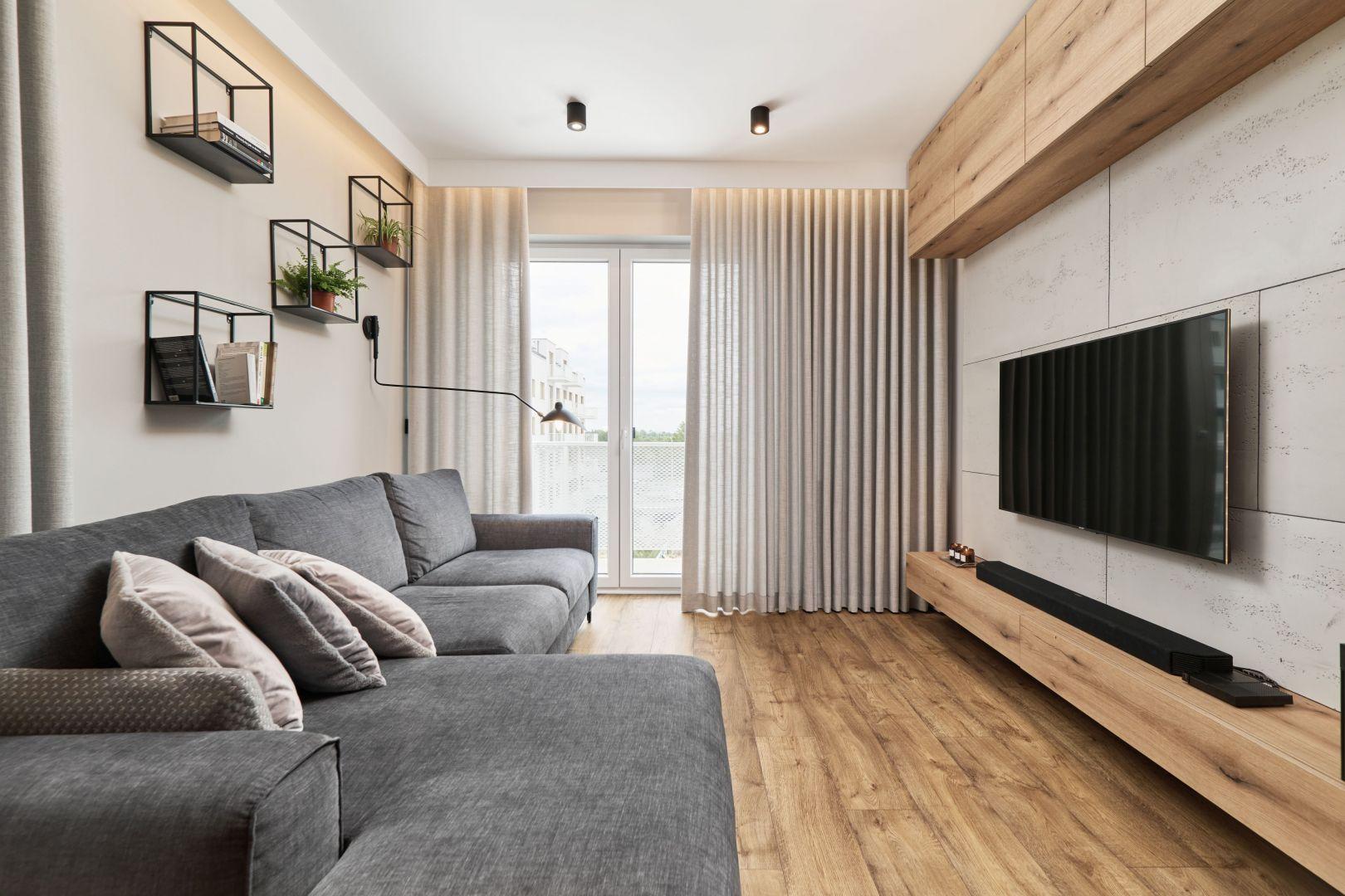 Nowoczesny salon z szarą kanapą, betonem na ścianie i przytulnymi panelami na podłodze. Projekt: Monika Staniec. Fot. Wojciech Dziadosz