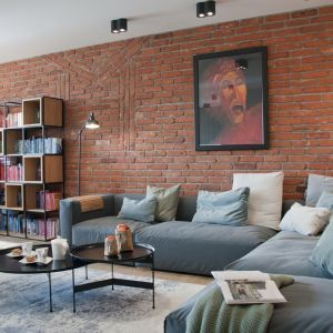 W nowoczesnym salonie połączonym z jadalnią dominującym elementem aranżacji jest czerwona cegła pochodząca z rozbiórki, która pięknie zdobi dwie ściany. Projekt: Ewelina Mikulska-Ignaczak, Mikulska Studio. Fot. Jakub Ignaczak, K1M1