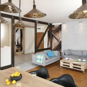 Surowe drewno w nowoczesnym salonie wspaniale współgra z betonem i stalowymi belkami. Projekt: Marta Kruk. Fot. Bartosz Jarosz