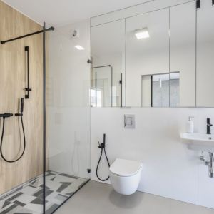 W łazience znajduje się prysznic typu walk-in z wzorzystymi płytkami na podłodze. Projekt: Decoroom. Fot. Marta Behling, Pion Poziom – fotografia wnętrz