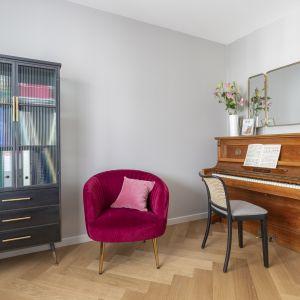 W apartamencie znalazł się także gabinet, w którym stanęło pianino właścicielki oraz biblioteczka i wygodny, burgundowy fotel.Projekt Decoroom Fot. Pion Poziom