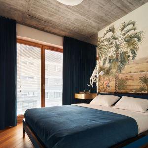 Ściana za łóżkiem w sypialni wykończona jest tapetą z motywem dżungli. Uzupełniają ją lampy w kształcie małp wspinających się ku sufitowi. Projekt: Karol Ciepliński, pracownia Blackhaus. Fot. Bartłomiej Sękowski