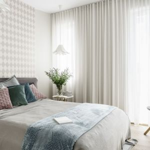 Ściana za łóżkiem w sypialni wykończona jest tapetą w jasnym kolorze i z delikatnym, subtelnym wzorem. Projekt: Joanna Morkowska-Saj, Saje Architekci. Fot. Fotomohito