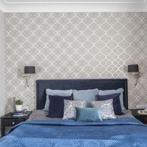 Ściana za łóżkiem w sypialni wykończona jest klasyczną tapetą w biało-szarym kolorze. Projekt: Decoroom. Fot. Pion Poziom