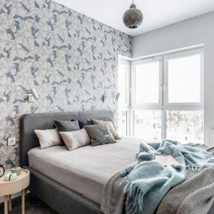Ściana za łóżkiem w sypialni wykończona jest tapetą inspirowana naturą. Jej chłodna kolorystyka świetnie pasuje do szarego, tapicerowanego łóżka. Projekt Magdalena Bielicka, Maria Zrzelska-Pawlak, pracownia Magma. Fot. Fotomohito