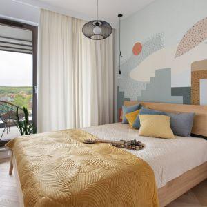 Ściana za łóżkiem w sypialni wykończona jest tapetą z kolorowym, geometrycznym wzorem. Projekt: Marta Kodrzycka, Marta Wróbel, Grupa Malaga. Fot. Magdalena Łojewska
