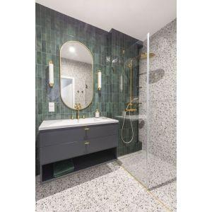 Małą łazienkę z prysznicem wykończono płytkami w kolorze butelkowej zieleni. Podłogę i ściany zdobią płyty z modnym motywem lastryko. Projekt: Decoroom Fot. Pion Poziom