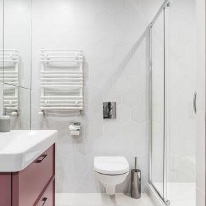Małą łazienkę z prysznicem urządzono w bieli. Ożywiają ją meble w odcieniu różu. Projekt: JT Grupa. Fot. Foto&Mohito