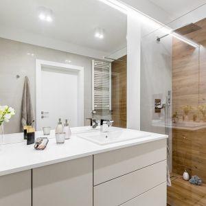 Mała łazienka z kabiną prysznicową typu walk-in. Duże lustro, białe meble oraz błyszcząca faktura płytek optycznie powiększają wnętrze. Projekt: Joanna Nawrocka. Fot. Łukasz Bera