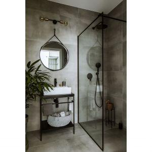 Łazienka, choć niewielka, mieści duży i wygodny prysznic walk-in. Bazę stworzyły wielkoformatowe płytki gresowe o strukturze betonu. Projekt: Poco Design. Fot. Yassen Hristov