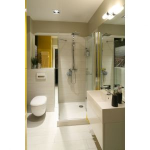 Mała łazienka z prysznicem w jasnych kolorach. Ponieważ drzwi prysznica składają się do środka, obok kabiny pozostało miejsce na zabudowę stelaża podtynkowego oraz sporą szafkę z umywalką. Projekt: Dorota Szafrańska. Fot. Bartosz Jarosz.