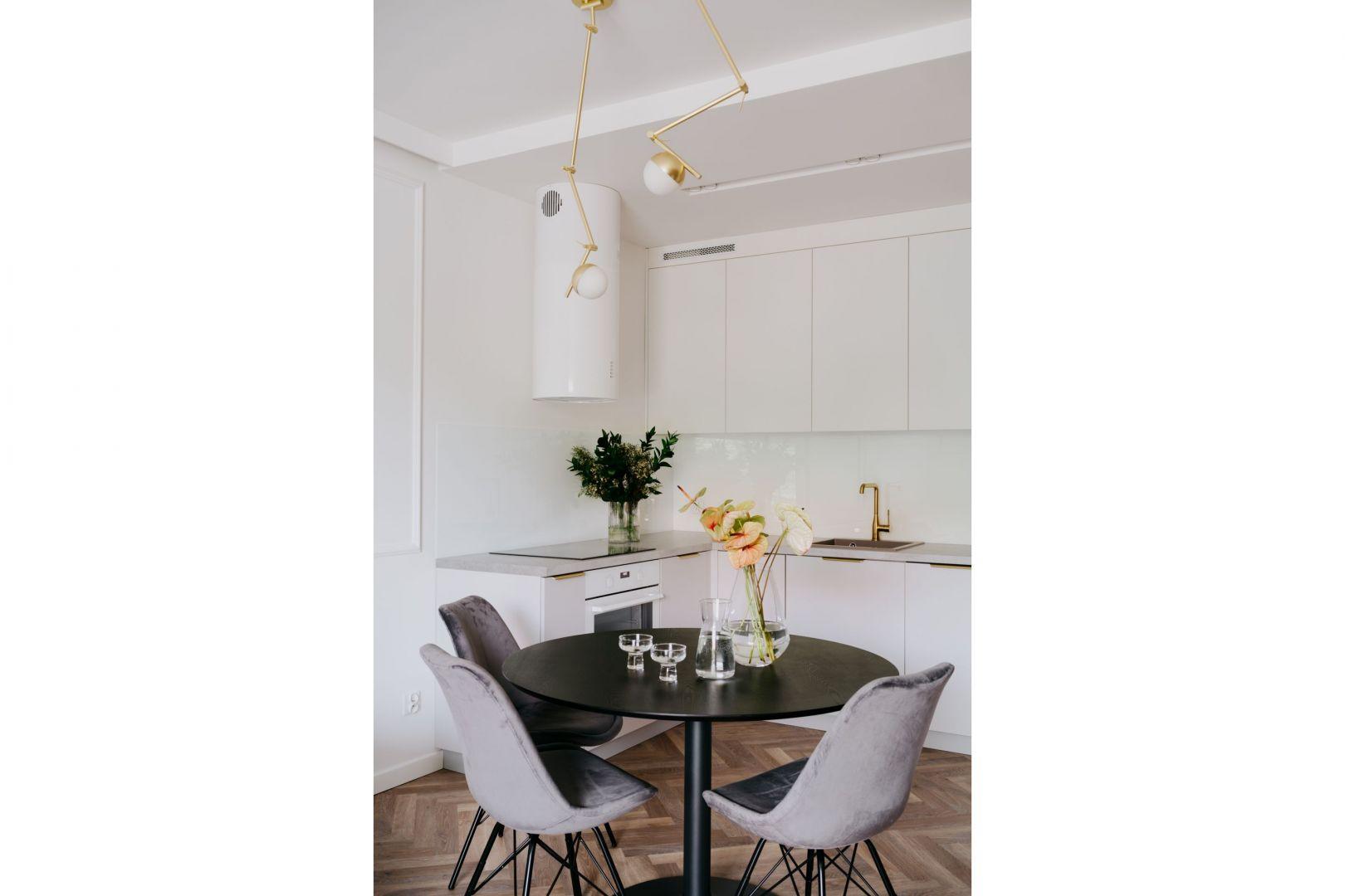 Stół można dowolnie przesuwać – projektantka postawiła bowiem na eleganckie lampy Contina Nordlux z oferty sklepu Ardant.pl z regulacją kąta nachylenia.