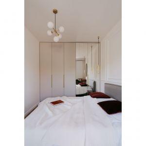 W sypialni znajduje się małżeńskie łóżko ze stolikami nocnymi, duża, autorska szafa z lustrami, które optycznie powiększają i multiplikują ścienny dekor.