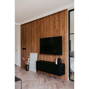 Ciepłą i bezpretensjonalną aranżację salonu wieńczy ściana wykończona imitacją drewna.
