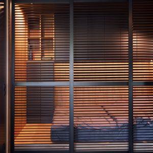 Sypialnia ukryta za drewnianymi shuttersami. 29-metrowa kawalerka w Poznaniu. Projekt wnętrza: 2form. Zdjęcia: Norbert Banaszyk