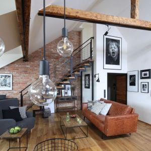 Ważną rolę w loftowym salonie odgrywa oświetlenie – minimalistyczne lampy czy nawet prosta żarówka zawieszona na kolorowym kablu w tej aranżacji zrobią niesamowite wrażenie. Projekt właściciele Fot. Bartosz Jarosz