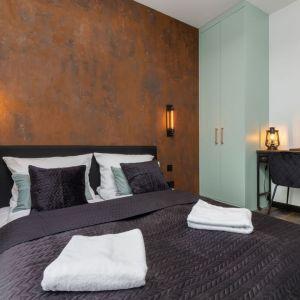 Ściana za łóżkiem w sypialni wykończona jest tynkiem w kolorze patyny i rdzy. Projekt: Aneta Subda. Fot. Renters. Współpraca: Dekorian Home