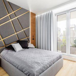 Ściana za łóżkiem w sypialni wykończona jest efektownym wezgłowiem. Oryginalne tapicerowanie zostało poprzecinane złotymi listwami. Projekt: Beata Napierała, pracownia Modify - Architektura Wnętrz. Fot. Michał Młynarczyk