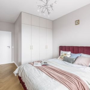Ściana za łóżkiem w sypialni wykończona jest farbą w jasnym, szarym kolorze, na której tle pięknie prezentuje się kolorowe wezgłowie łóżka. Projekt: Decoroom Fot. Pion Poziom