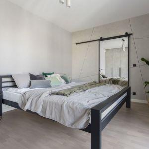 Ściana za łóżkiem w sypialni wykończona jest dekoracyjnym tynkiem przywodzący na myśl beton. Projekt: Decoroom. Fot. Marta Behling, Pion Poziom – fotografia wnętrz