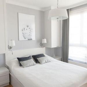 Ściana za łóżkiem w sypialni wykończona jest farbą. Na jasnym tle świetnie wygląda nowoczesna grafika i kinkiety ze stylowymi abażurami. Projekt: Studio Projektowania Miśkiewicz Design. Fot. Anna Powałowska