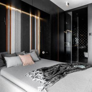 Ściana za łóżkiem w sypialni wykończona jest szarym, tapicerowanym zagłówkiem z ciepłego, miękkiego filu, który dodatkowo, pocięty został pasami forniru i miedzi. Projekt: pracownia Magma. Fot. Fotomohito