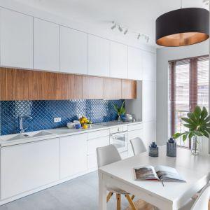 Białą kuchnię pięknie ożywia niebieska mozaika. Projekt: Monika Pniewska. Fot. Pion Poziom