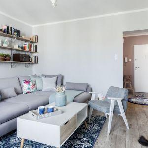 Szara sofa w skandynawskim stylu i pasujący do niej stolik na drewnianych nogach. Projekt Justyna Mojżyk. Fot. Monika Filipiuk  Obałek