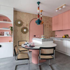 Niewielka jadalnia znajduje się tuż przy kuchni, w której uwagę zwracają fronty w kolorze pudrowego różu. Realizacja i zdjęcia: KODO Projekty i Realizacje Wnętrz