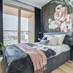 Ściana za łóżkiem w sypialni wykończona jest ciemną tapetą strukturalną Nakuru projektu Wonderwall Studio. Projekt: Olga Nowosad-Szewców, Decoroom. Fot. Pion Poziom