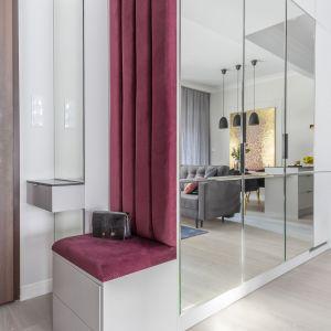 Przedpokój z tapicerowanym siedziskiem i lustrzaną szafą. Projekt i zdjęcia: KODO Projekty i Realizacje Wnętrz