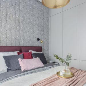 Geometryczna tapeta na ścianie za łóżkiem w sypialni. Projekt i zdjęcia: KODO Projekty i Realizacje Wnętrz