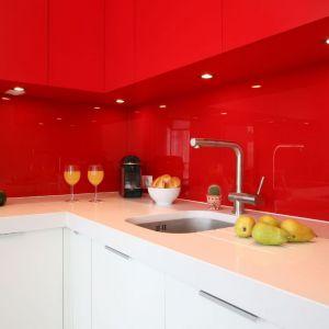 Ściana nad blatem w kuchni wykończona jest szkłem w czerwonym kolorze. Projekt: Iza Szewc. Fot. Bartosz Jarosz