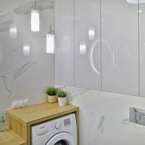 W łazience wygospodarowano miejsce na pralkę oraz na pojemne szafki. Projekt: Beata Ignasiak, pracownia Ignasiak Interiors. Fot. Grupa Deix