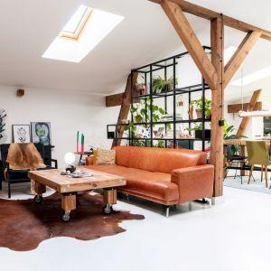 W jednym z narożników poddasza znalazła się strefa wypoczynkowa, odgrodzona od jadalni ażurowym regałem z metalu, wkomponowanym między belki wspierające dach. Projekt wnętrza: Szalbierz Design. Zdjęcia: Maja Musznicka Shine Studio