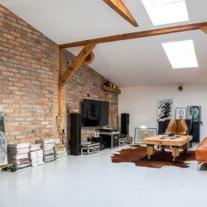 Ściany w salonie wykończone są białą farbą oraz cegłą. Projekt: Szalbierz Design. Fot. Maja Musznicka Shine Studio