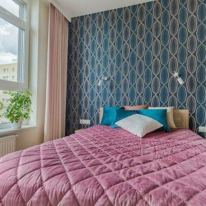 Ściana za łóżkiem w sypialni wykończona jest tapetą z wyraźnym wzorem, nadającym wnętrzu charakter. Projekt: Beata Ignasiak, pracownia Ignasiak Interiors. Fot. Grupa Deix