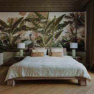 Ściana za łóżkiem w sypialni wykończona jest oryginalną tapetą. Na ścianach widzimy dżunglę pełną zwierząt i wielkolistnych roślin. Projekt: JT Grupa. Fot. ONI studio
