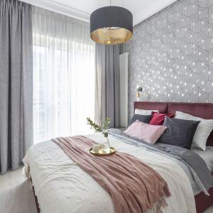 Ściana za łóżkiem w sypialni wykończona jest tapetą o geometrycznym wzorze. Projekt i zdjęcia: KODO Projekty i Realizacje Wnętrz
