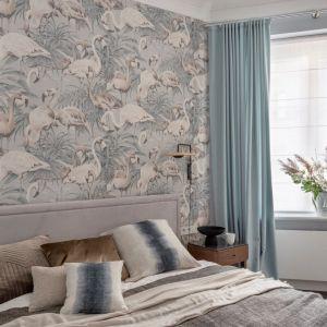 Ściana za łóżkiem w sypialni wykończona jest jasną tapetą z flamingami. Projekt: Maria Jachalska. Fot. Marcin Grabowiecki. Stylizacja: Eliza Mrozińska