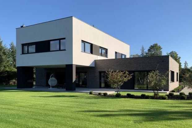 Ten nowoczesny dom z płaskim dachem został zbudowany na dużej, pięknejdziałce. Jego elegancka, prosta forma ubrana wnaturalną cegłę i biały tynk delikatnie wpisuje się w otoczenie.